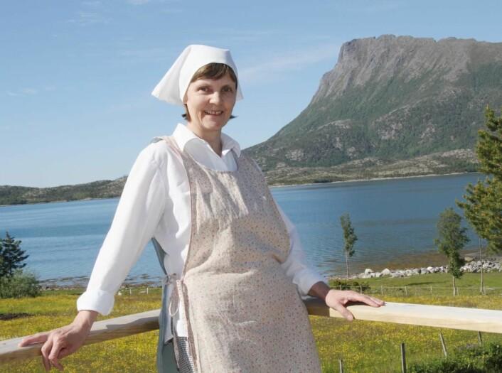 Anita Vik på serveringsterrassen, der gjestene kan nyte både havet og midnattssolen. (Foto: Morten Holt)