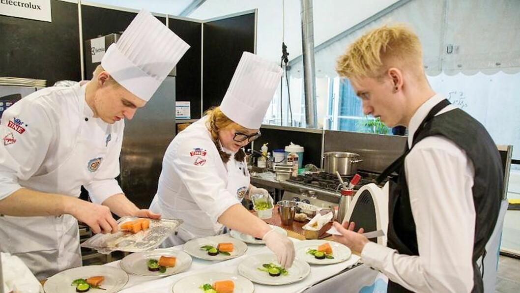 Elevene Ruben Lund og Marte Bekkedal Limam fra Nannestad videregående skole legger opp mat, og kontrolleres av Daniel Skedsmo. (Foto: Nannestad videregående skole)