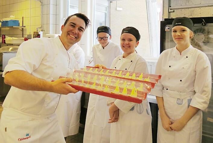 Pynten til desserten er klar. Tine-konditor Bernhard Azinger med de lærevillige tilskuerne Nina, Suzanne og Elisabeth. (Foto: Janne Sandvik)