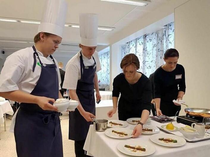 Kokkelærlingene Simen Buvik (til vesntre) og Tord Johnsæter og servitørlærlingene Maria Suarez og Maria Moldver (til høyre) i gang med å flambere dessert under helgens nordiske mesterskap i Helsinki. (Foto: NHO Reiseliv)