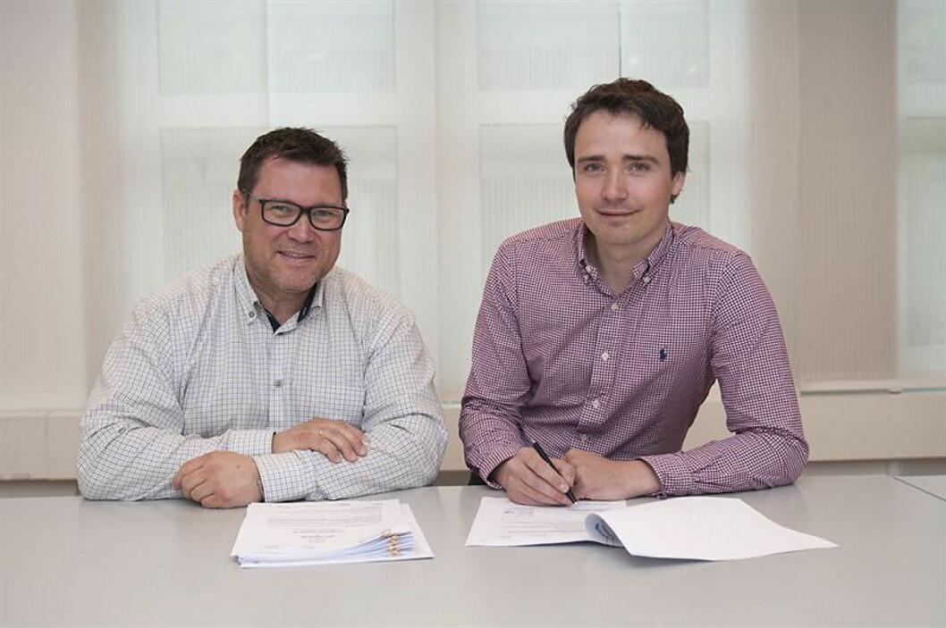 Erik Nyfelt, energiselger i Hafslund Varme, og Jarle Andersen, rådgiver for energi og tekniske anlegg i Olav Thon signerer avtalen om leveranse av fjernvarme.