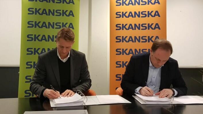 Sven Kruse-Jensen (prosjektsjef Bane NOR Eiendom) og Tor Arne Midtskogen (regiondirektør Skanska Bygg Oslo Næring) signerer kontrakten. (Foto: Skanska)