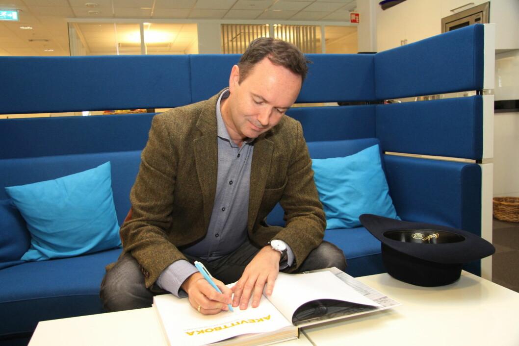Arnt R. Steffensen signerer nok en akevittbok. (Foto: Morten Holt)