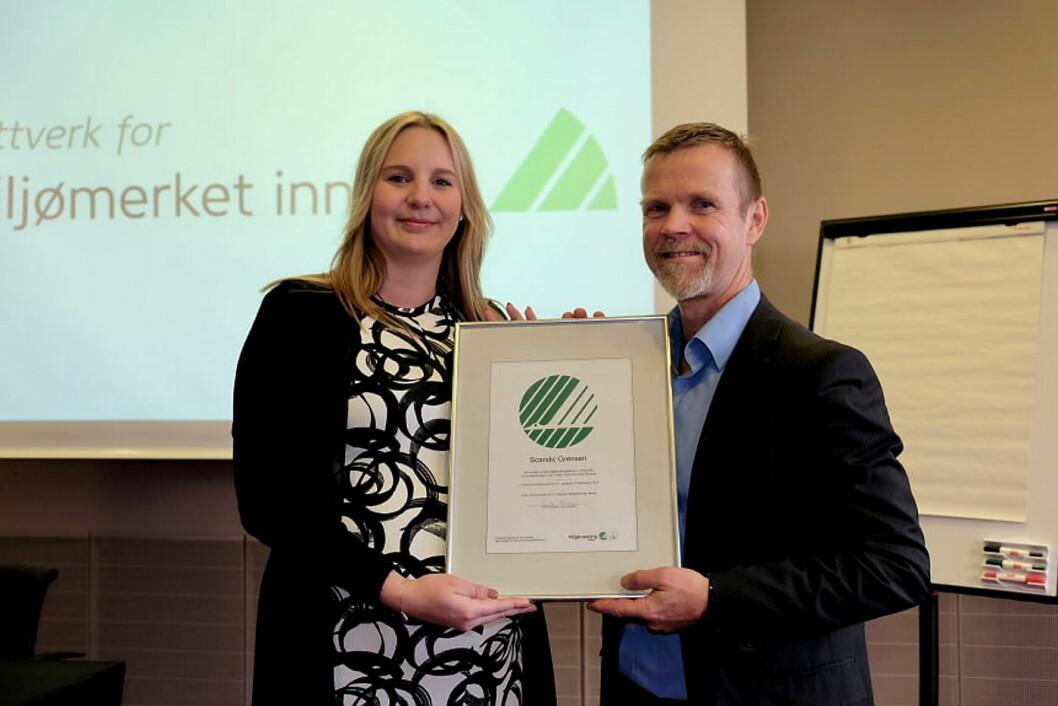Therese Fredriksson, hotellsjef på Scandic Grensen, mottar bevis på at hotellet har blitt sertifisert med Nordens offisielle miljømerke fra Tormod Lien, Svanemerket. (Foto: Svanemerket)