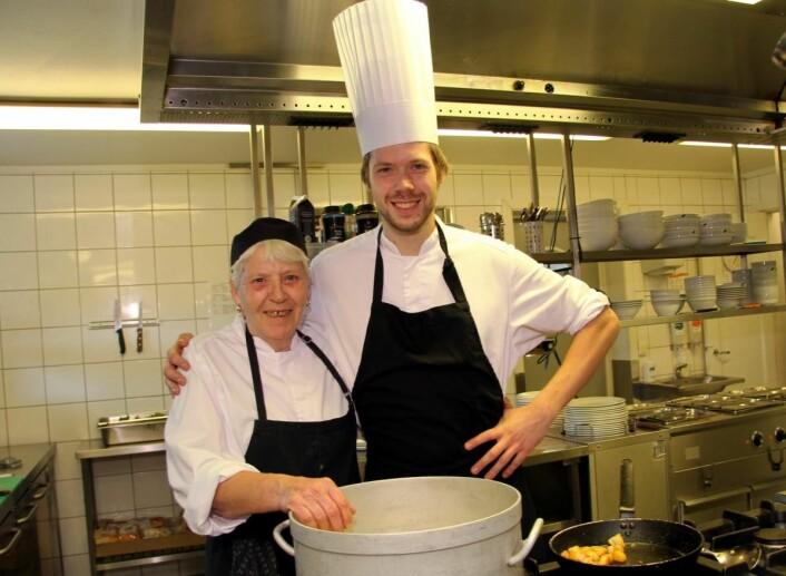 Venke Myhre har 46 års fartstid, 40 av dem sammenhengende, på kjøkkenet på Elgstua, og har mange gode råd å bidra med når lærlingene skal læres opp. Her sammen med kjøkkensjef Jan Erik Pedersen. (Foto: Morten Holt)