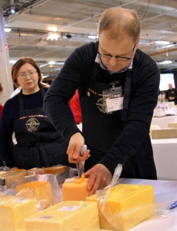 Dommer Arne Sørvig tar kjerneprøve fra én av ostene. Dommerne tar slike prøver av alle ostene før de bedømmes. (Foto: Morten Holt)