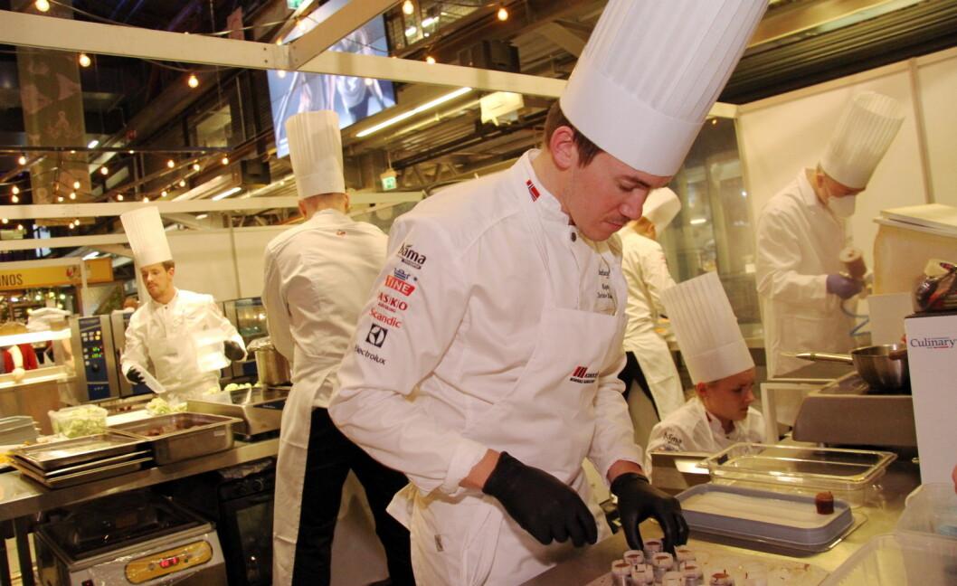 Christer Rødseth, til daglig kjøkkensjef på Vaaghals, er kaptein på det norske kokkelandslaget. Bak er alle de andre fem kokkene i arbeid. (Foto: Morten Holt)