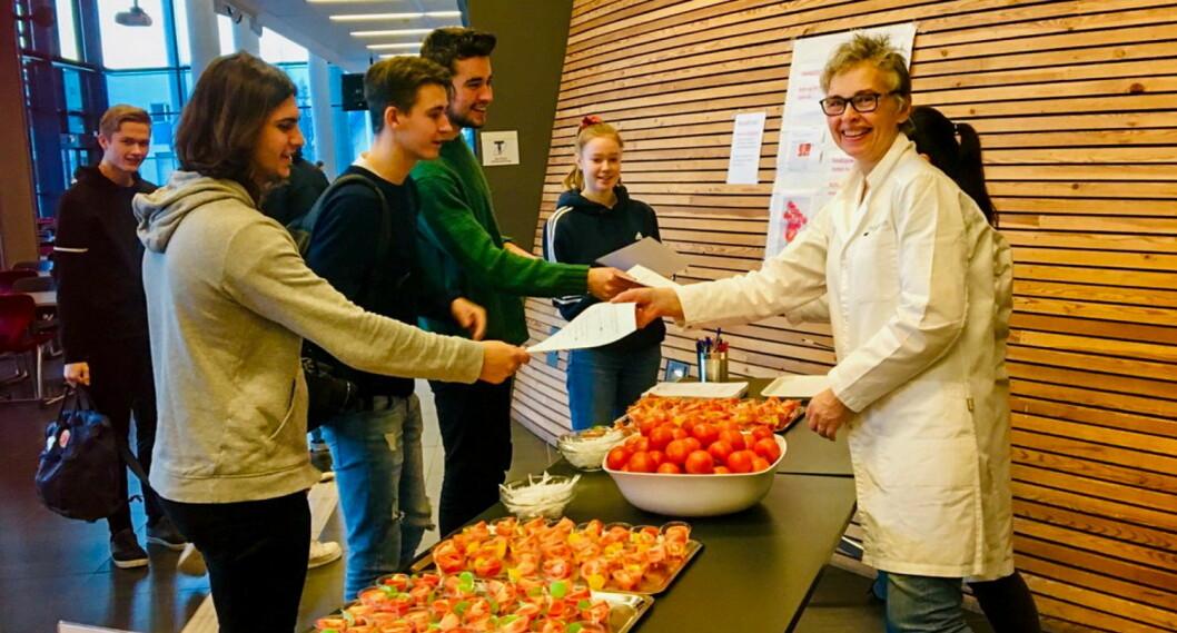 Nofima-forsker Jorunn Sofie Hansen (t.h.) mottar besvarelser fra elever ved Vågen vgs. Kantinen deres var én av fem som deltok i omfattende forbrukerundersøkelse om norsk og utenlandsk tomat. (Foto: Jorunn Sofie Hansen/Nofima)