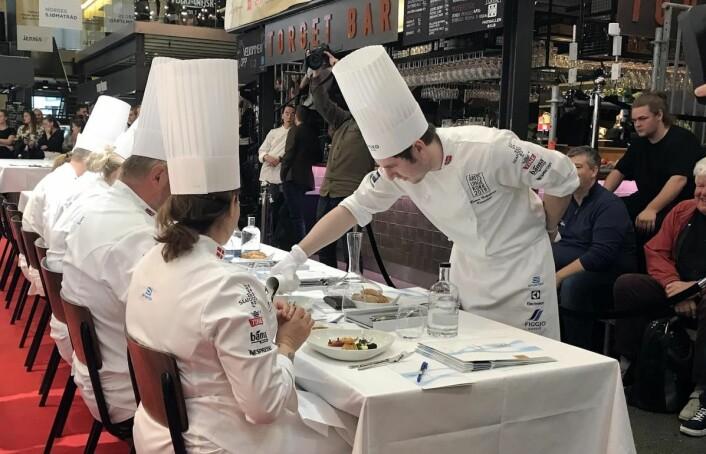Runar Helgeland, en av deltakerne i Årets unge kokk, serverer saus til juryen.