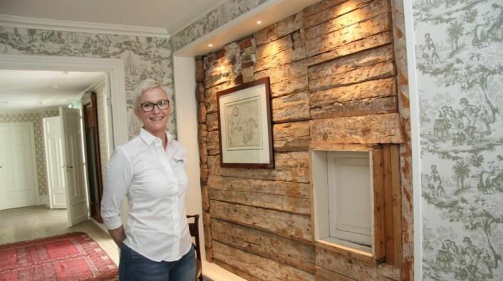 Den gamle tømmerveggen er bevart i Reymerts hus, viser hotelldirektør Therese Malmo. (Foto: Morten Holt)