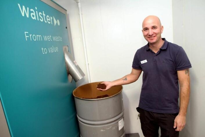 Teknisk sjef på Støtvig Hotel, Ragnar Riordan, viser hvordan matavfallet blir til et tørt pulver, som kan sammenlignes med kaffegrut. (Foto: Morten Holt)