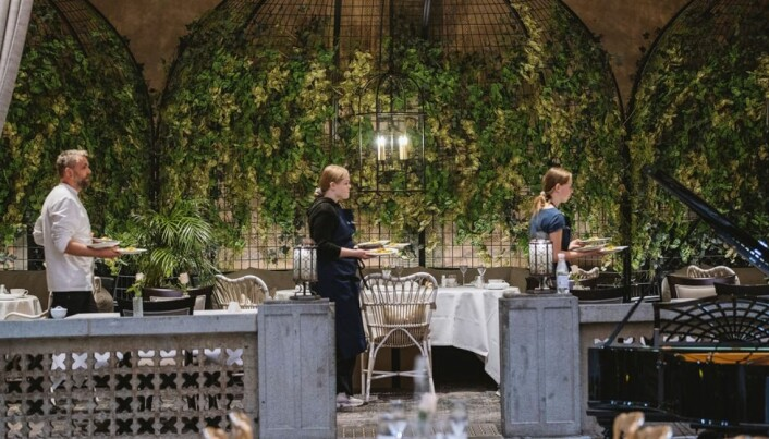 Det er klart for servering på Britannia Hotel. Elever fra Rosenborg ungdomsskole retter seg opp i ryggen og bærer tallerkener som profesjonelle servitører. De har lært av de beste. (Foto: Matriketmidt.no/Wil Lee Wright)