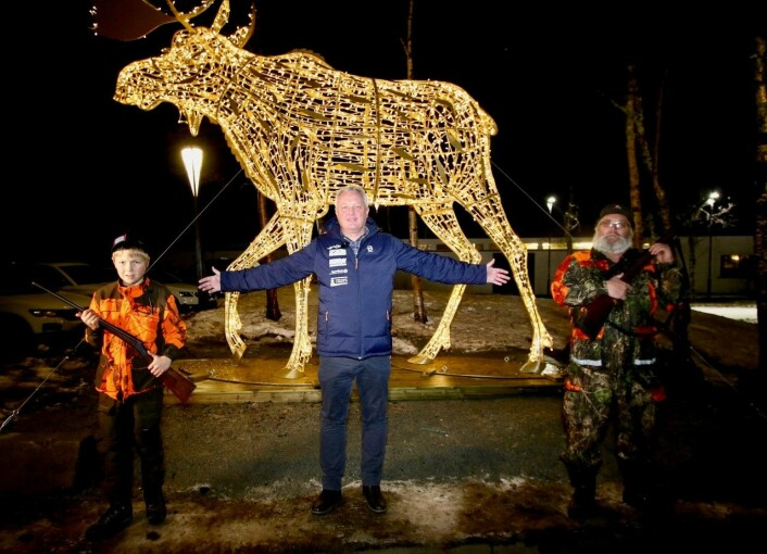 Ordfører i Øystre Slidre, Odd Erik Holden, tente lyset på elgen utenfor Radisson Blu-hotellet på Beitostølen. Til venstre elgjegertalentet Amund Helle Larsen (11) og til høyre den mer garvede elgjegeren Øystein Rudi.(Foto: DestinasjonsKirurgene)